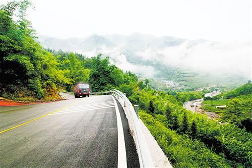 近日,万盛经开区江流坝旅游公路,汽车在云雾掩映下的公路上行驶.